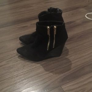 Black suede booties with gold zippers